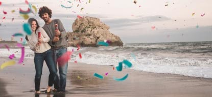 A couple setting off handheld confetti cannons on the beach