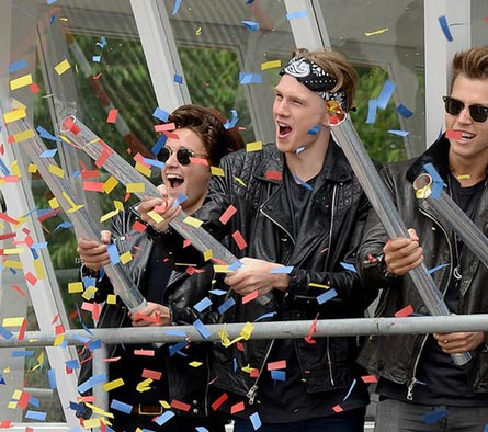 Three boys setting off large handheld confetti cannons